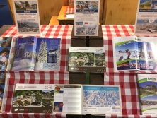 Prospektpräsentation am Messestand Urlaub in den Alpen